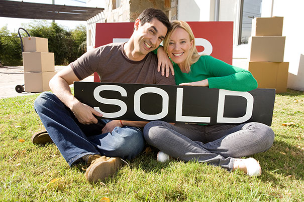 couple with sold sign in front of new home